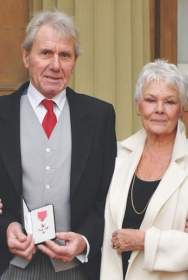 David Mills, the partner of Dame Judi, receiving the MBE for services to wildlife conservation