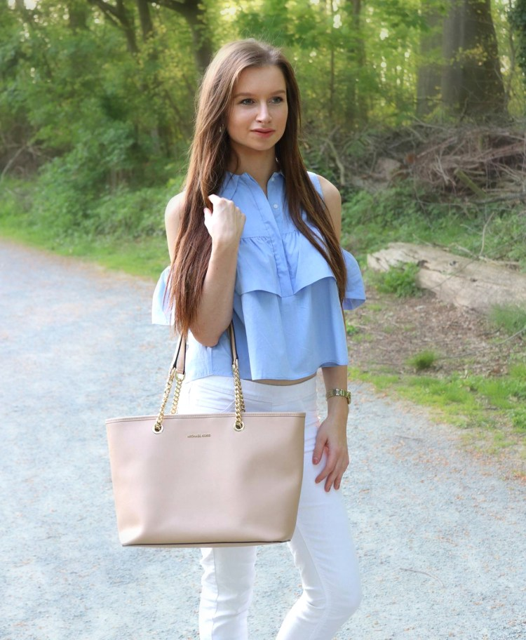 Blue ruffled blouse with white jeans and Michael Kors bag