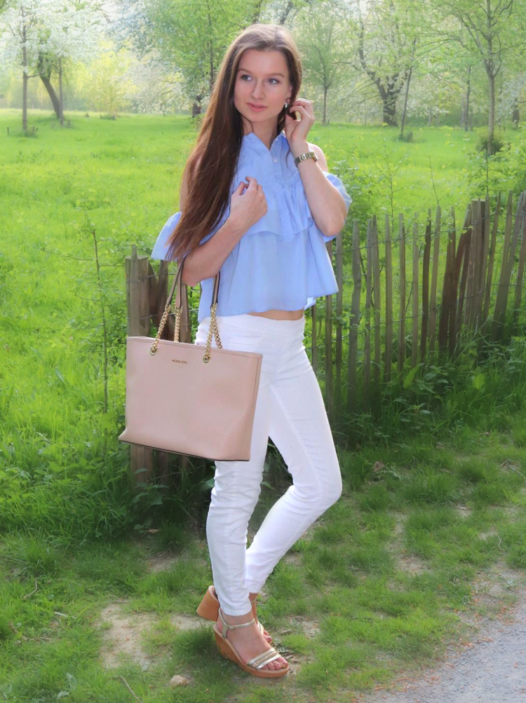 Pastel blue ruffled blouse with white skinny jeans and beige Michael Kors bag