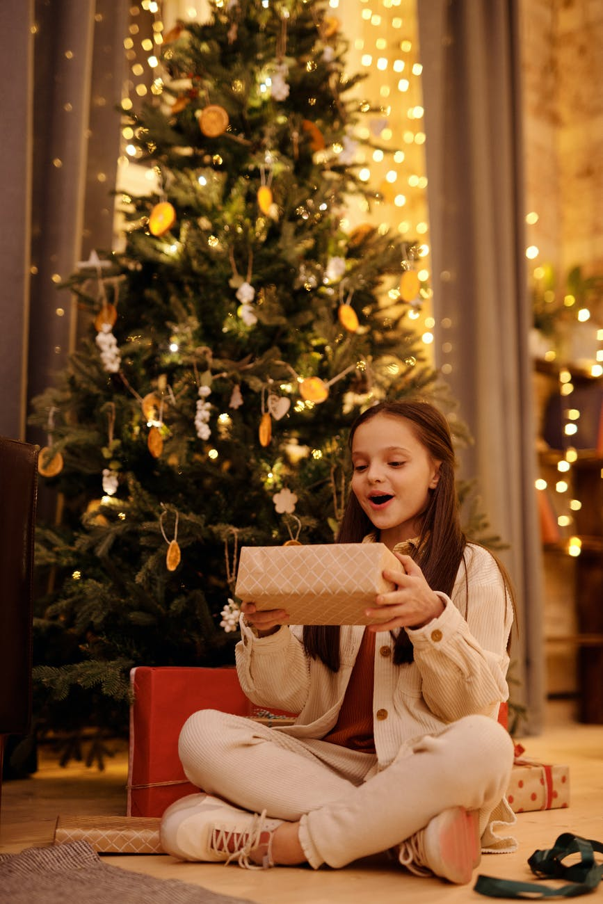 excited girl with gift box near christmas tree at home