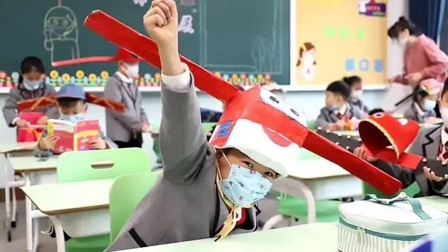 Kindergarten student in China, wearing his meter hat to socially distance himself from classmates