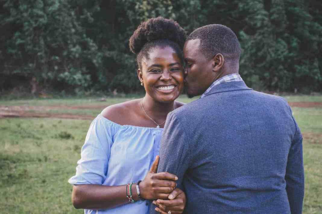 man kissing left cheek of smiling woman