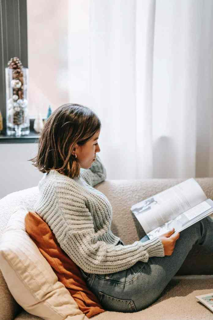 focused ethnic woman leaning on cushions and reading book