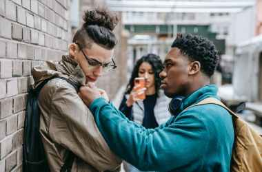 multiracial students having argument on city street