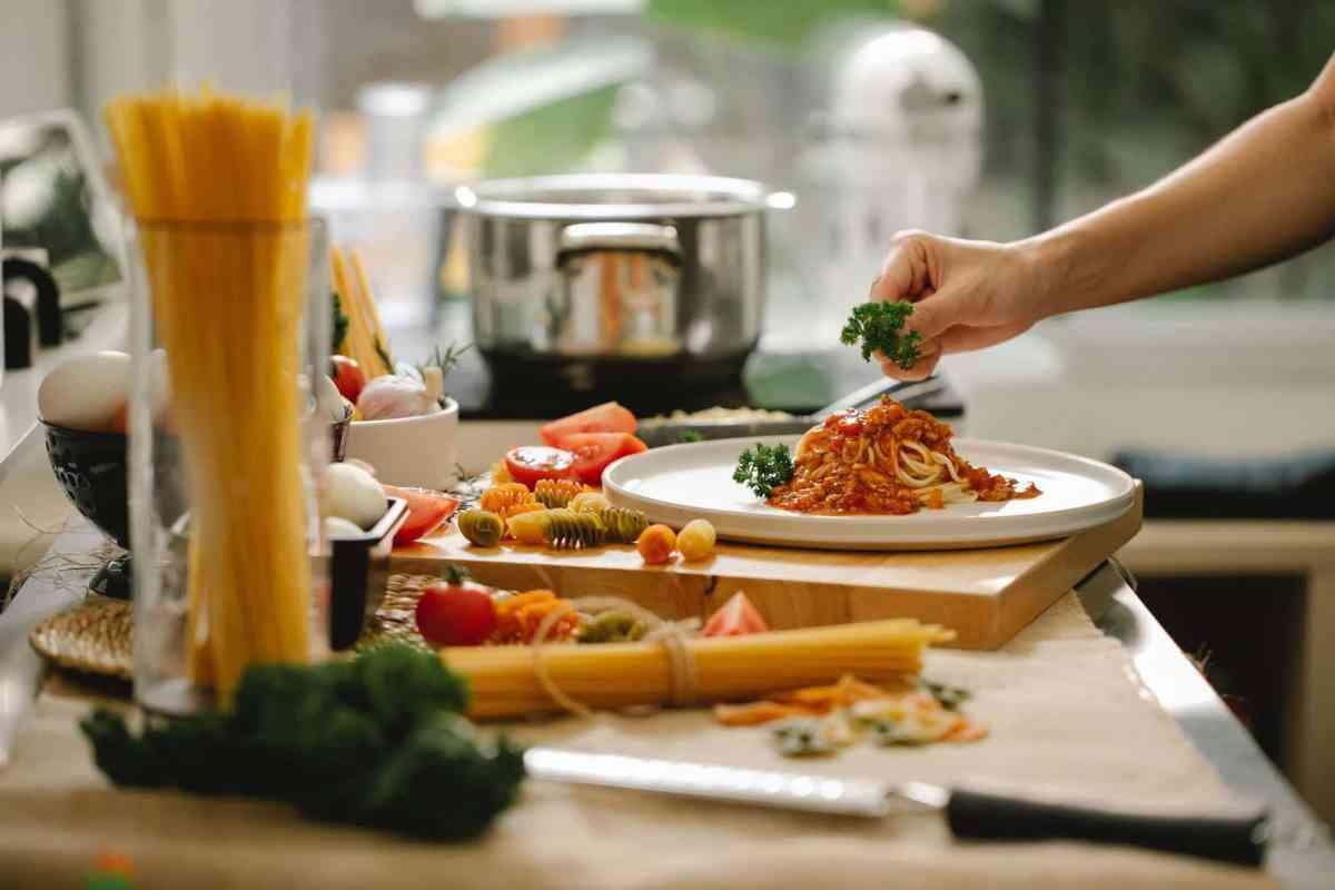 cook adding greens to pasta in kitchen