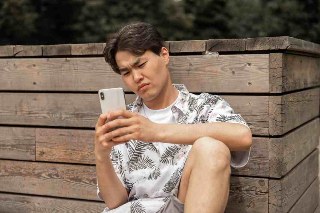 asian displeased man browsing smartphone in countryside
