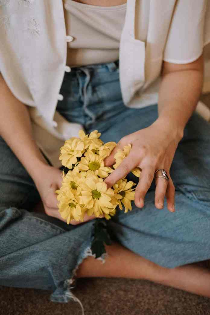crop faceless woman sitting on floor with bunch of chrysanthemums