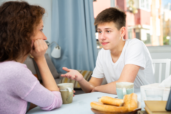 Mother and teenage son talking