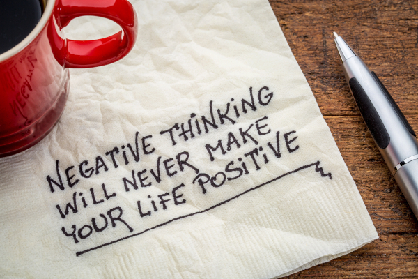"""""""Negative thinking will never make your life positive"""" - inspirational handwriting on a napkin with a cup of coffee"""