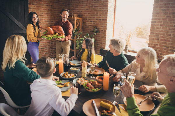 Couple serving turkey to family gathering