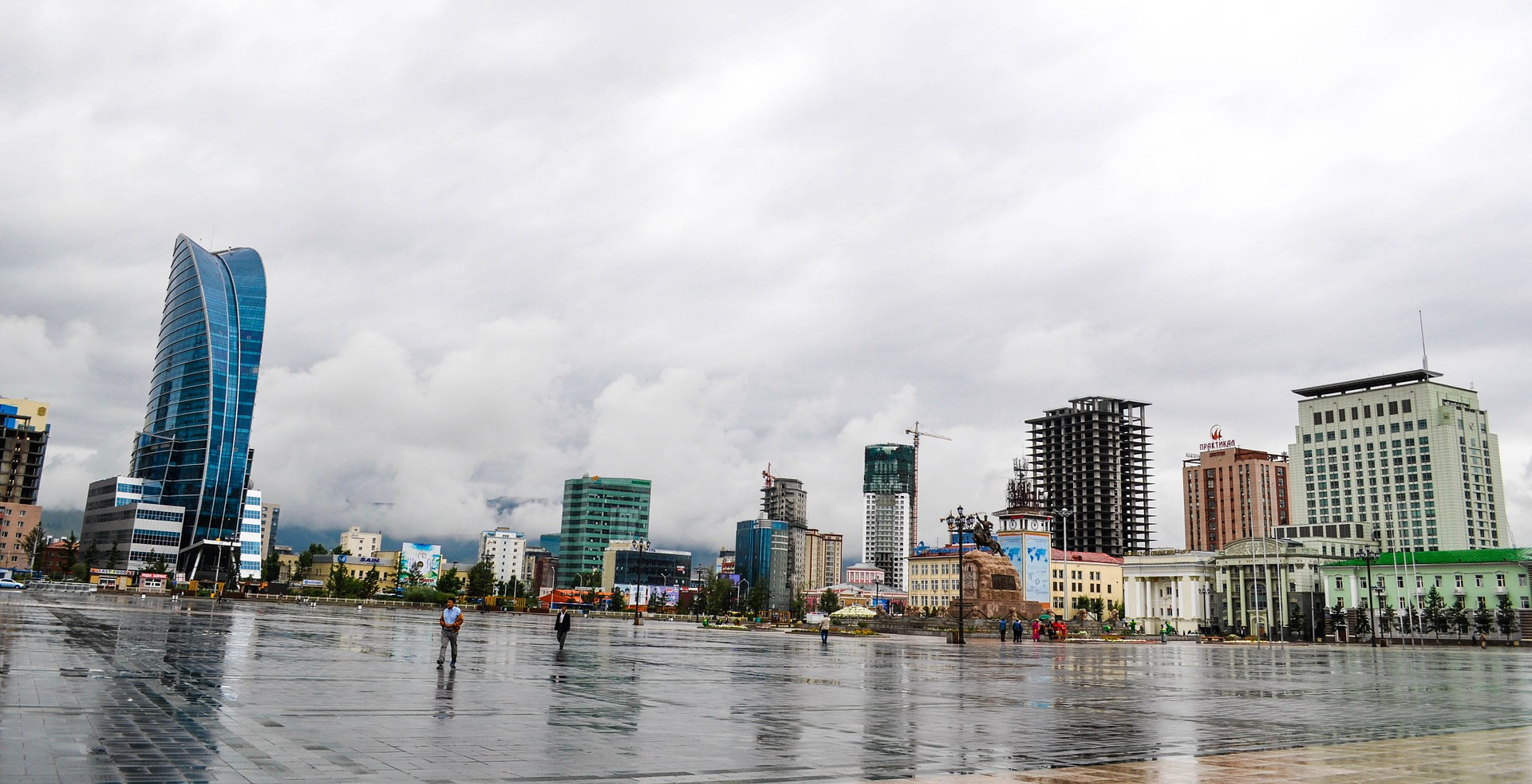 paved square in Ulaanbaatar and several tower in the background in front of a grey, cloudy sky