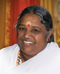 Amma is with a gathering of her children at a rest stop on tour and smiles sweetly at everyone.