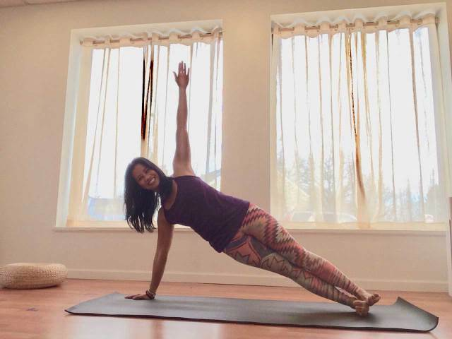 A yoga teacher in a side plank, with arms stretched into a t shape