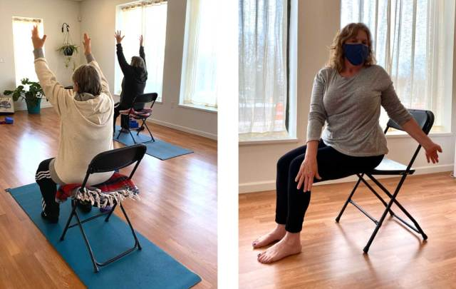 Two senior adults practice yoga stretches in chairs in class