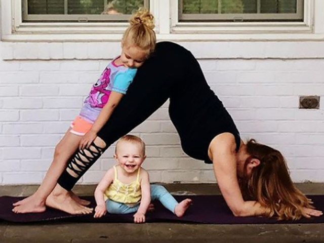 A yoga student in downward dog with a baby under their belly and another kid leaning on their legs