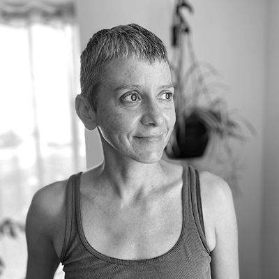 A yoga instructor headshot looking off in the distance at the yoga house studio
