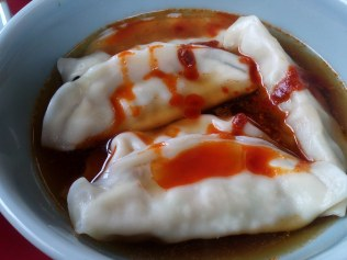 Boiled gyoza with added soy sauce and chili oil.