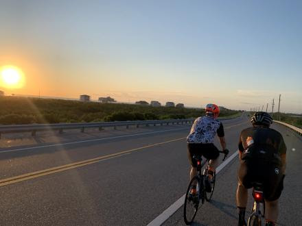 two cyclists riding into sunset
