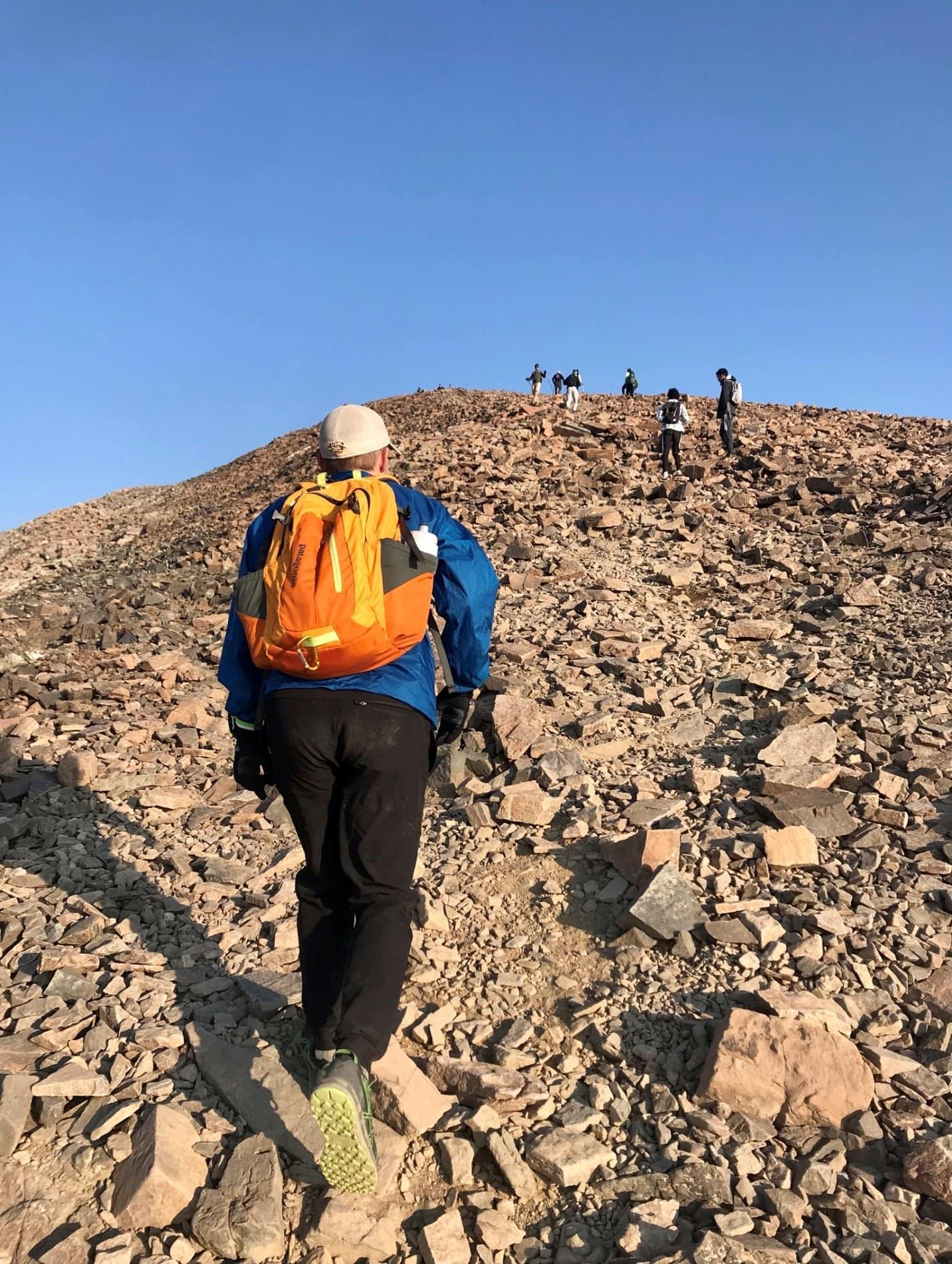 hikers climbing up a mountain