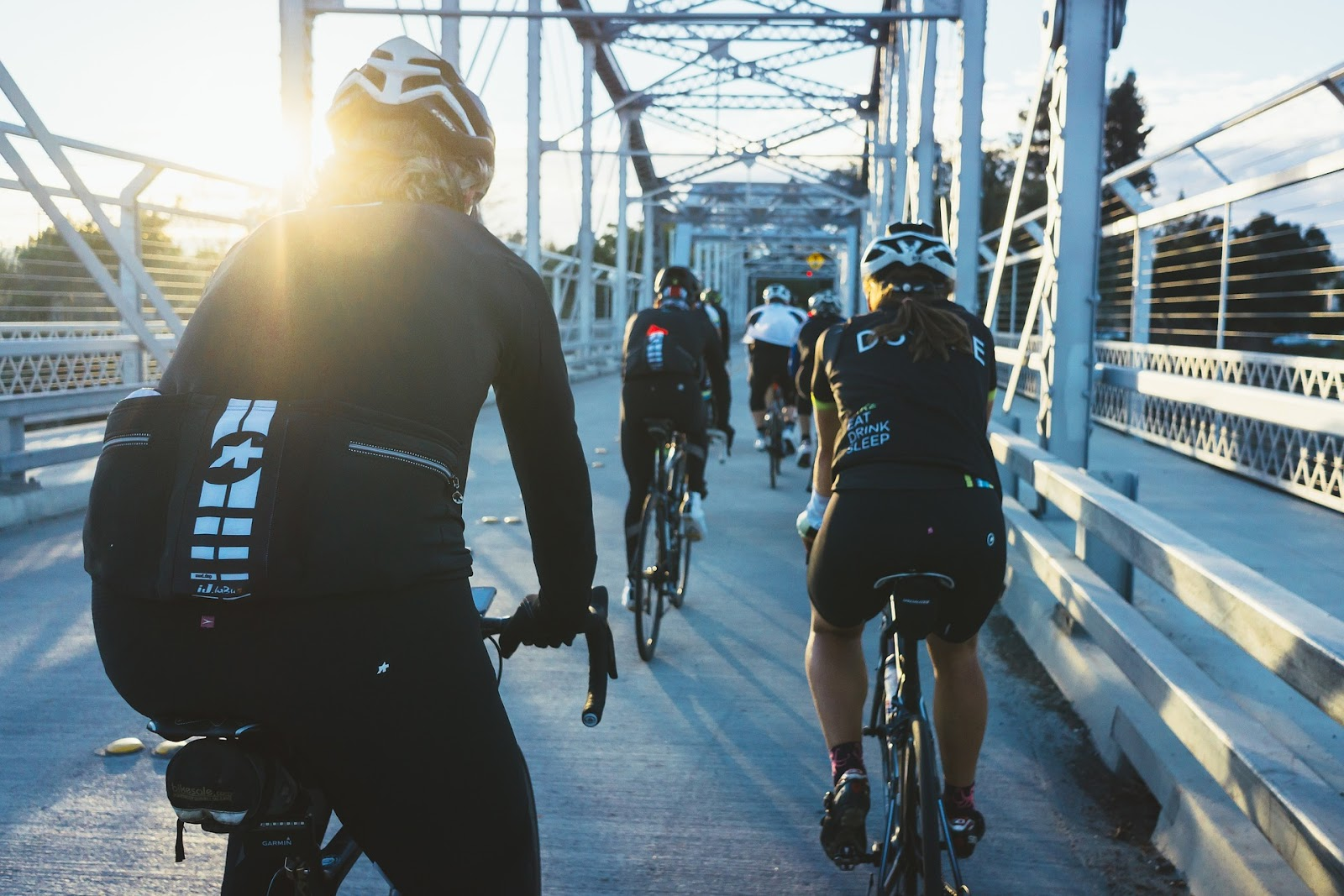 cyclists riding on a bridge with back to camera