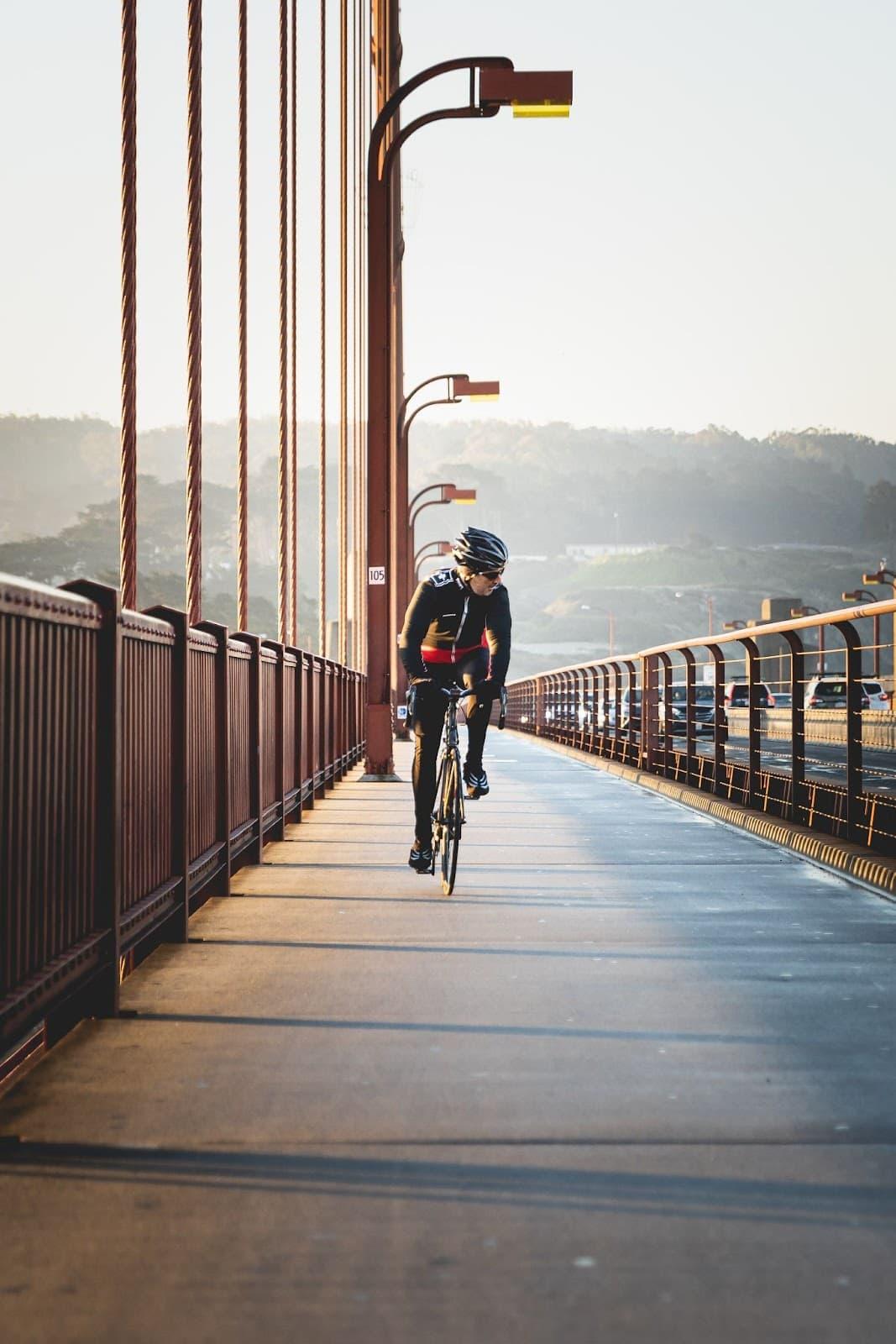 cyclist riding on bridge towards camera