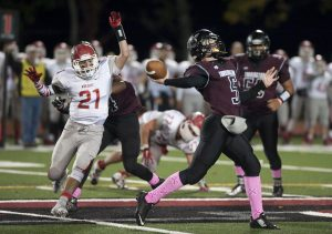 Torrington's Connor Finn (5) throws a pass while Wolcott's Brad Grasso (21) puts on some pressure  during their game Friday at Torrington High School. Jim Shannon Republican-American