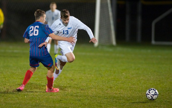 Lorenz Gunzl (13) gets tripped up by Tolland's Aiden Devaney (26) during their Class M. semifinal game Wednesday at Tunxis Mead Sports Complex in Farmington. Jim Shannon Republican-American