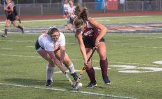 Watertown field hockey player Frankie Mancini tries to shoot past Pomperaug player Katie Burstiner. (RA)