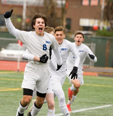 Lewis Mills' Dylan McCall (8) celebrates his game-winning goal with teammates in their 3-2 win over Suffield to capture the Class M state title Saturday at Willow Brook Park in New Britain. Jim Shannon Republican-American