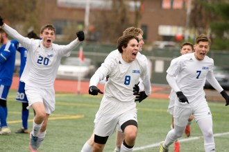 Lewis Mills' Dylan McCall (8) celebrates his game-winning goal with teammates in their 3-2 win over Suffield to capture the Class M state title Saturday at Willow Brook Park in New Britain. (RA)