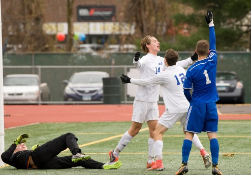 Lewis Mills' John Mudgett (14) celebrates with teammate Matt Gilbert (12) after scoring the game-tying goal during their Class M state final game against Suffield Saturday at Willow Brook Park in New Britain. Jim Shannon Republican-American