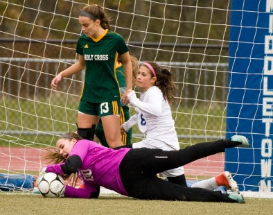 Holy Cross' Tori Schaffner makes a diving save in front of Old Lyme's Grace Lathrop (8) and teammate Madison Bushka (13), during their Class S state final game Saturday at Middletown High School. Jim Shannon Republican-American