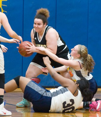 Kaynor Tech's comes up with a loose ball after a battle with Wolcott Tech's Katiusca Delacruz (30) and Katie Benedict (21) during their game Thursday at Wolcott Tech school in Torrington. Jim Shannon Republican-American