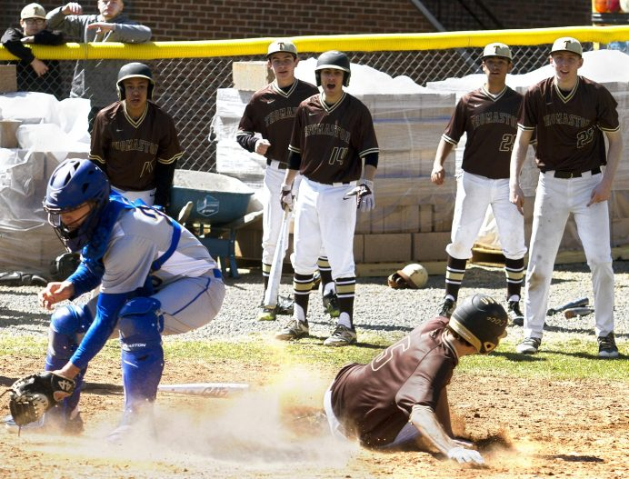 THOMASTON, CT - 31 MARCH - 033118JW14.jpg -- Thomaston baseball players cheer as #5 Keegan Daigle slides home during Thomaston's 5-3 win over Gilbert Saturday afternoon. Jonathan Wilcox Republican-American