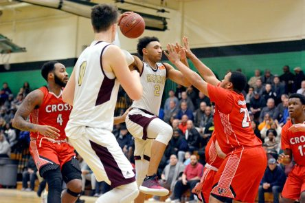 Sacred Heart's Isiah Gaiter (2) slides in to put up a shot in front of Wilbur Cross' William Antrum (24) during their Division I quarterfinal game Monday at Wilby High School in Waterbury. Jim Shannon Republican-American