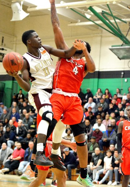 Sacred Heart's Raheem Solomon (11) gets a shot off while holding back Wilbur Cross' Jaykeen Foreman (4) during their Division I quarterfinal game Monday at Wilby High School in Waterbury. Jim Shannon Republican-American