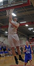 Northwestern Regional's Jayson Reola ( 10 ) puts up a lay up as Lewis Mills' Joe Neary (24) looks on during the Division IV state tournament quarterfinals Monday night at Northwestern Regional High School. Northwestern defeated Lewis Mills 58 -35 Michael Kabelka / Republican-American