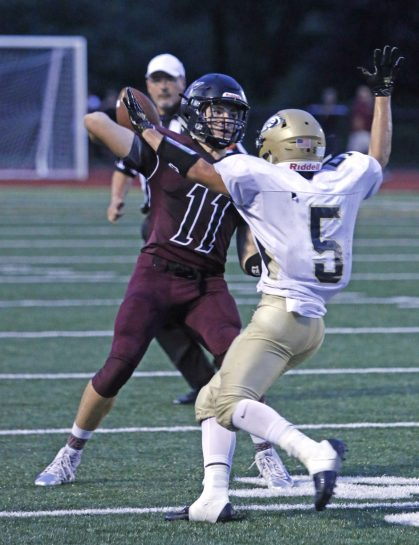 Torrington's Ora Curry (11) gets off a pass under pressiure from Woodland's Zack Cochran (5) during NVL action at Torrington High School Friday night. Woodland defeated Torrington Michael Kabelka / Republican-American
