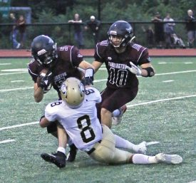 Torrington's Jacob Coleman (5) is brought down by Woodland's Jason Palmieri (8) in the backfield during NVL action at Torrington High School Friday night. Woodland defeated Torrington Michael Kabelka / Republican-American
