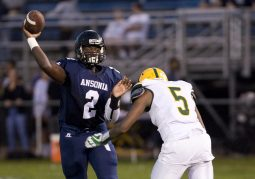Ansonia's Sheldon Schuler (2) gets a pass off while being pressured by Holy Cross' Marcus Payne(5) during their game Friday at Nolan Field in Ansonia. Jim Shannon Republican American