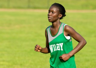 Wilby's Rebecca Adhiambo crosses the finish line during their meet with Holy Cross, Torrington and Kennedy Wednesday at Holy Cross High School in Waterbury. Jim Shannon Republican American