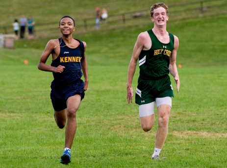 Kennedy's Derek Yates overtakes Holy Cross' Ben Bowler at the finish line to take second place during their meet with Torrington and Wilby Wednesday at Holy Cross High School in Waterbury. Jim Shannon Republican American