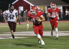 Wolcott High School's Jake Sforza runs the ball ahead of Torrington High School's Jacob Allen during the varsity football game in Wolcott on Friday. Emily J. Reynolds. Republican-American