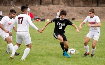 Kaynor Tech's Erick Silva (12) slips between a trio of Goodwin Tech players during their game Monday at Kaynor Tech High School in Waterbury. Jim Shannon Republican American