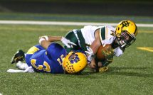 Holy Cross High School's Connor Goggin holds on to the ball as he is tackled by Seymour High School's Tyler Ganim during the varsity football game in Seymour on Friday. Emily J. Reynolds. Republican-American