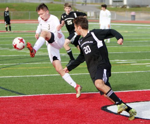 #3 Adam Ortiz of Joel Barlow kicks a ball past #20 Matt Karp of Pomperaug High during Soccer action in Southbury Friday. Steven Valenti Republican-American