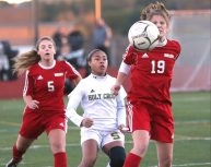 Wolcott High School's Morgan Matyoka knocks the ball down in front of Holy Cross High School's Jasmine Thorpe during the NVL Girls' Soccer Tournament semi-final girls varsity soccer game in Watertown on Tuesday. Emily J. Reynolds. Republican-American