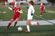 Wolcott High School's Bella Piacentini and Holy Cross High School's Devon Bushka battle for the ball on the sideline during the NVL Girls' Soccer Tournament semi-final girls varsity soccer game in Watertown on Tuesday. Emily J. Reynolds. Republican-American