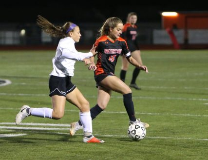 Woodland Regional High School's Aries Bell and Watertown High School's Meadow Mancini battle for the ball during the NVL Girls' Soccer Tournament semi-final girls varsity soccer game in Watertown on Tuesday. Emily J. Reynolds. Republican-American