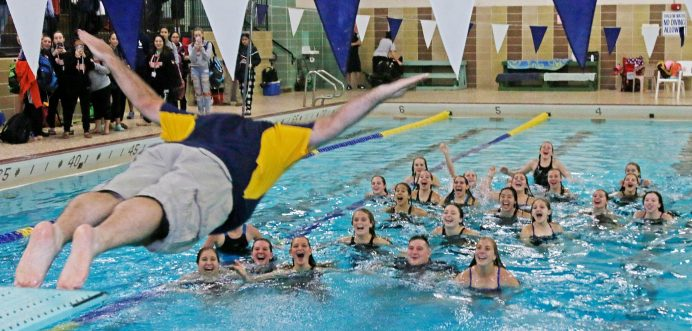Seymour's coach Patrick DiCaprio dives towards his 2018 NVL champion girls swimteam at Kennedy High School Friday night. Seymour won the NVL title with an overall score of 755.5. Michael Kabelka / Republican-American